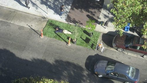 Picture of man laying on lawn inside parking spot