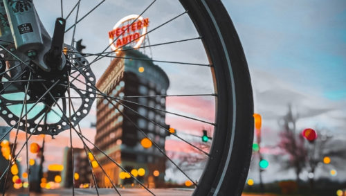 Picture of bike wheel and Western Auto building.