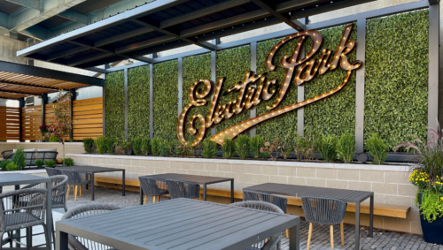 """Pictured is the patio seating area with a greenery wall and """"Electric Park"""" marquee sign."""