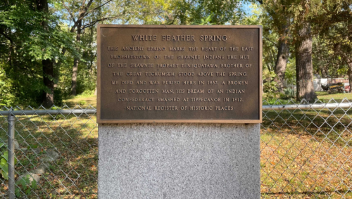 A plaque stands in front of the private property where White Feather Spring runs.
