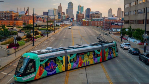 A colorful Streetcar sits diagonally on the road with the downtown Kansas City skyline in the distance.